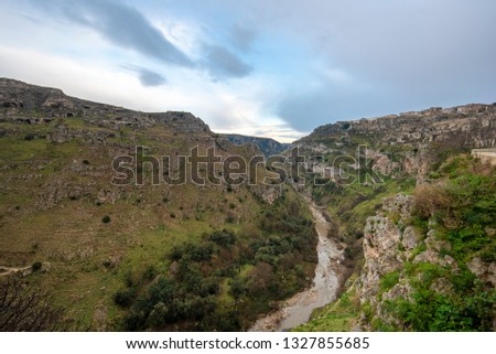 The prehistoric sassi caves, caverns and dwellings are visible in the hillside across the canyon ravine in the Basilicata city of Matera, Italy. the Gravina river's canyon in the area #1327855685