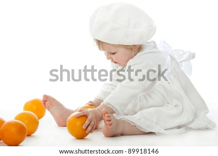 The pretty barefooted baby girl is playing with ripe oranges on white background.
