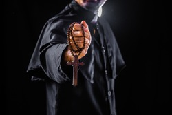 The priest holds the cross on black background For Halloween concepts
