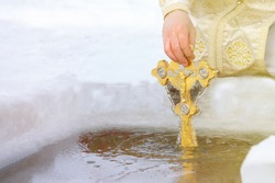 The priest sanctifies the water cross in the hole on the feast of the Baptism of the Lord. Traditional rite of consecration of water on Epiphany