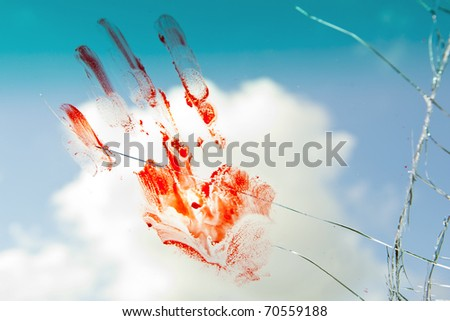 The print of a bloody handpalm on the cracked window of a car. (the greener area on top is the sun shade of the windscreen) - stock photo