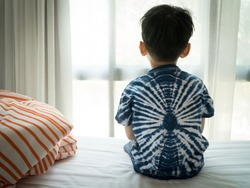 The Problem of Child Development:A little boy sitting by the bed looking through the window Absent-minded. Recognizing Developmental Delays in Children, Autism awareness, Psychological trauma Kids.