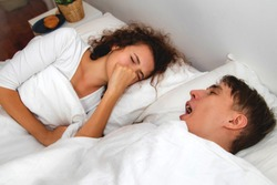 The problem of the bad breath of a young man creates a nuisance for his girlfriend during sleeping together until using his hands to close his nose