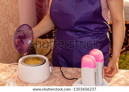 The procedure for preparing the cabinet and equipment, tools for waxing. The beautician prepares the room and preparations to work to remove unwanted body hair.