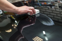 The process of applying a nano-ceramic coating on the car's hood by a male worker with a sponge and special chemical composition to protect the paint on the body from scratches, chips and damage.