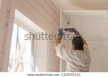 The process of assembling furniture, the master assembles a white cabinet using an electric drill in a room with a white wooden finish in the Scandinavian style.