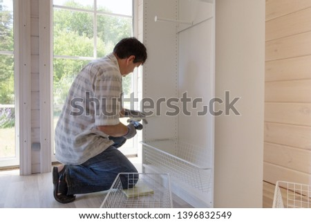 The process of assembling furniture, the master assembles a white cabinet using an electric drill