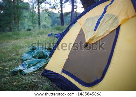 The process of Assembly and installation of a tourist tent. Arc tents and stakes lie on the ground next to the stretched tent. #1465845866