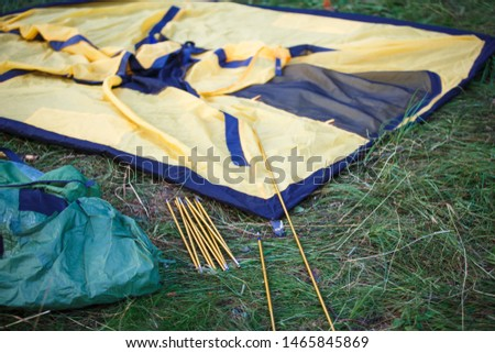 The process of Assembly and installation of a tourist tent. Arc tents and stakes lie on the ground next to the stretched tent. #1465845869