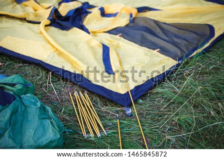 The process of Assembly and installation of a tourist tent. Arc tents and stakes lie on the ground next to the stretched tent. #1465845872