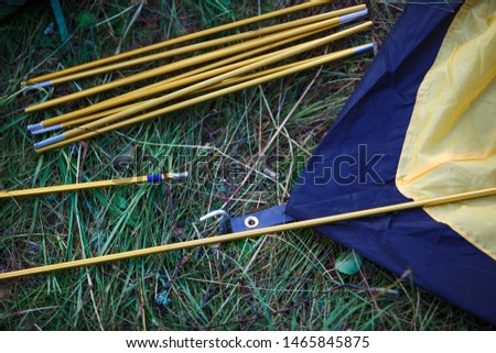 The process of Assembly and installation of a tourist tent. Arc tents and stakes lie on the ground next to the stretched tent. #1465845875