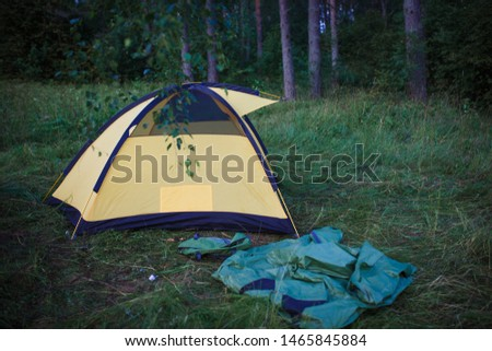 The process of Assembly and installation of a tourist tent. Arc tents and stakes lie on the ground next to the stretched tent. #1465845884