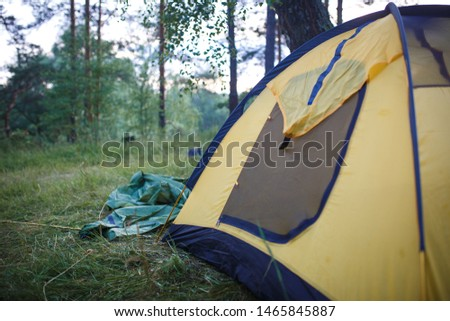 The process of Assembly and installation of a tourist tent. Arc tents and stakes lie on the ground next to the stretched tent. #1465845887