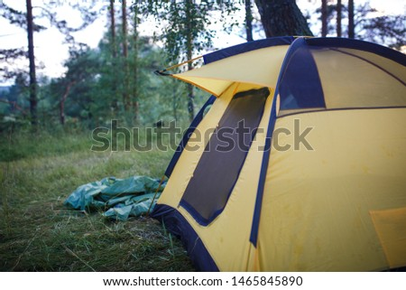 The process of Assembly and installation of a tourist tent. Arc tents and stakes lie on the ground next to the stretched tent. #1465845890