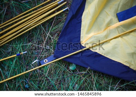 The process of Assembly and installation of a tourist tent. Arc tents and stakes lie on the ground next to the stretched tent. #1465845896