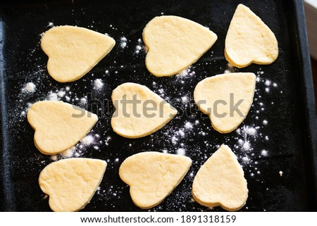 the process of baking cookies in the shape of a heart. The concept of the Valentine's Day holiday.On a black background made of heart dough. Stock photo ©