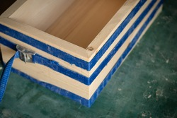 The process of box joints use tie down straps clamping to pull all the joints tight. Making wooden box in the carpentry workshop. Pinewood boards with bevel cut on the cutting mat.