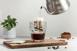 The process of brewing coffee. Water is poured into a drip coffee bag in a mug. Trends in brewing coffee at home.