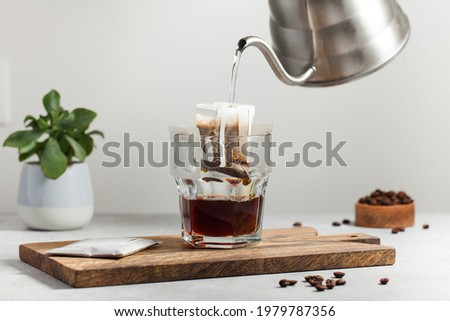 The process of brewing coffee. Water is poured into a drip coffee bag in a mug. Trends in brewing coffee at home. Photo stock ©