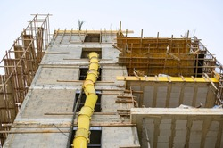 The process of building a residential building. Scaffolding, yellow chute, safe waste disposal. Open facade. View from below. Horizontal view. Urban view.