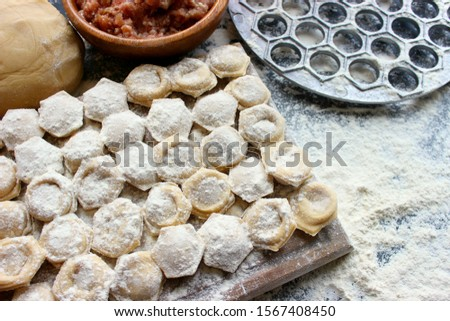 The process of cooking homemade dumplings. Homemade raw ravioli on a wooden Board. The dumpling making. Russian national home-cooked food. Copy space.