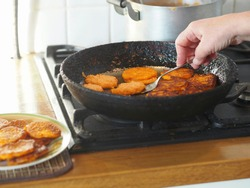 The process of cooking pumpkin pancakes at home in a pan on a stove. Diet healthy homemade food made from natural ingredients.