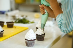 The process of decorating chocolate cupcakes with airy protein cream. Creation of cakes by professional pastry chefs.