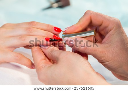 The process of doing a manicure in the spa salon. Applying red nail polish on the nails in the nail salon. Manicure, hand care, nail care, red lacquer. The concept of hand care, nail beauty.