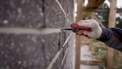 The process of hammering in the seams in the facade of the tiles. Grouting the seam on the facade of the building. A worker sews seams on the facade of a building. building.