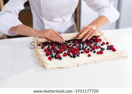 The process of making a meringue roll. The pastry chef prepares a meringue roll. Cooking meringue roll in the kitchen. Meringue roll with strawberries and blueberry ストックフォト ©