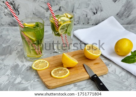 The process of making lemonade. On a wooden Board is a Lemon and mint next to a knife. There are glasses of lemonade in the background. Summer drink. Lemonade with lemon and mint. Selective focus