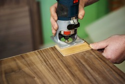 The process of milling edges on a veneer product. Making furniture with an electric edge router. Close-up