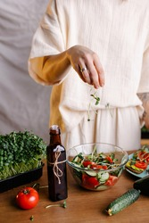 The process of preparing a salad with microgreens and natural oil. Add sprouts to food. Healthy food rich in vitamins and nutrients bio eco. Vegan bowl. Lifestyle kitchen table. Low calorie diet