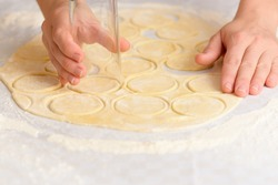 the process of preparing dough for dumplings, rolling out the dough and cutting circles with women's hands to sculpt dumplings on a light kitchen table.