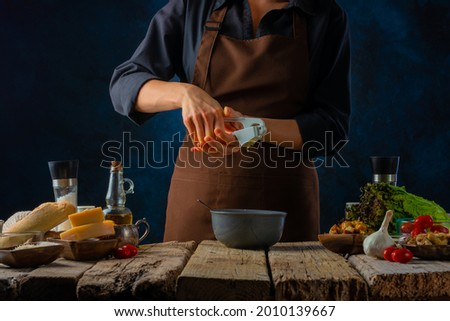 The process of preparing the dressing for the classic Caesar salad. The cook squeezes the garlic into the sauce. The products from which the Caesar salad will be prepared are on the table. Foto stock ©