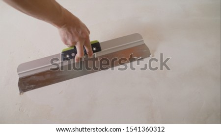 The process of putty the walls with a large spatula. Photo stock ©