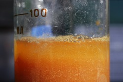 The process of separation of water-insoluble particles of iron oxalate in a beaker. The color of the colloidal solution is orange.