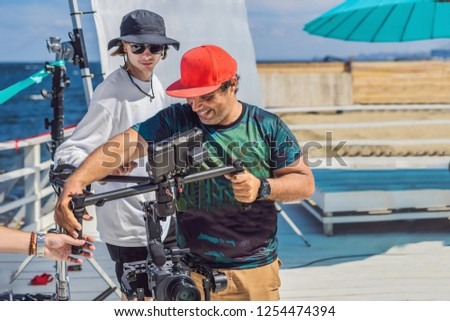the production team on a commercial video shoot. Steadicam operator uses the 3-axis camera stabilizer and cinema-grade camera