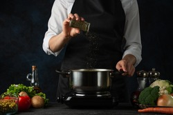 The professional chef in black apron adds spices into pot with soup on dark blue background. Backstage of cooking dinner. Preparing meal concept. Frozen motion.
