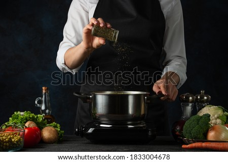 The professional chef in black apron adds spices into pot with soup on dark blue background. Backstage of cooking dinner. Preparing meal concept. Frozen motion. Stock photo ©