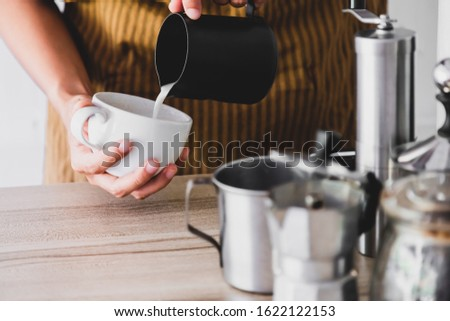 The professional of a barista poured milk. making hot coffee with equipment, tool brewing on bar at kitchen home