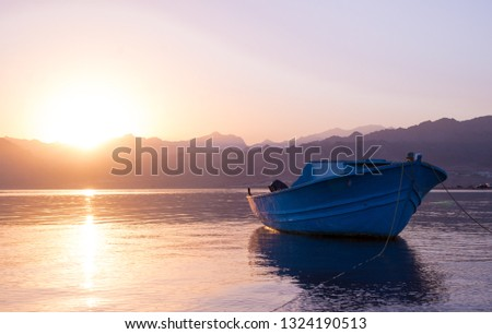 The profile of a boat. The rays of the sunset on the surface of the sea. Evening sea and mountains with boats on the horizon. Sunset landscape. Copy space