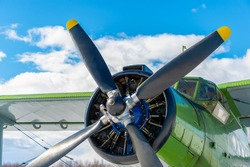 The propeller and engine of an old Soviet biplane on the background of the sky and clouds.Retro light airplane at the airport in nature. Air transportation of passengers and cargo.