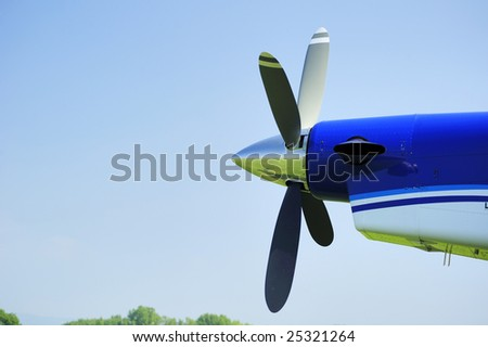 The propeller of an aircraft against a clear blue sky. The grass airstrip and sky can be seen reflected in the nose cone. Space for text in the blue sky.