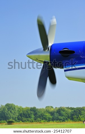 The propeller of an aircraft starting up, against a clear blue sky. Motion blur on the propeller blades.