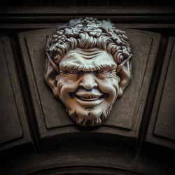 The protective mask on the top of a historical building entrance, the bas relief of satyr