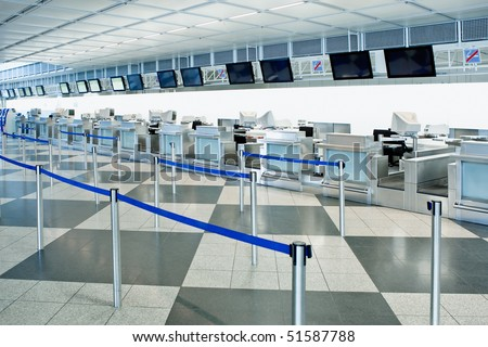 The public check-in area of an airport with crowd control barriers