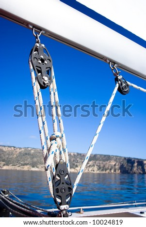 The pulleys on the boom of a sailboat.