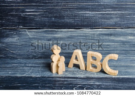 The pupil and pupils stand at the big letters ABC of the English alphabet. Parent and children. The concept of education and upbringing of children, instruction. Teacher and students. School #1084770422