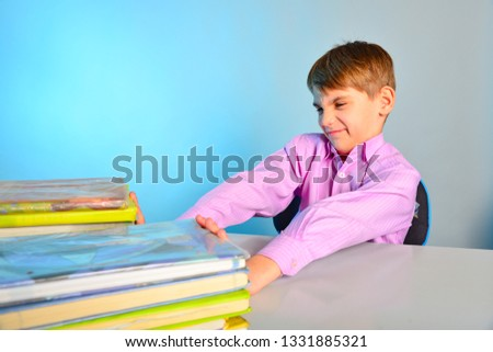 The pupil pushes the textbooks off with his hands, the tortured schoolboy does not like to learn.